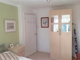 De ouder slaapkamer, het bed staat vrij met nachtkastjes aan weerskanten en een ruime kleding kast.