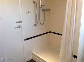Een ruime douche van 120 x 80 cm groot. Er is een steun beugel. Het opstapje is 21cm hoog.