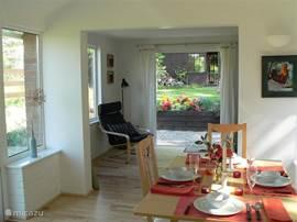 Een gezellige eethoek met licht van twee kanten. De eettafel kan worden uitgeschoven, dan is er ruimte voor 6 personen. De L vormige kamer leidt  naar de zithoek.