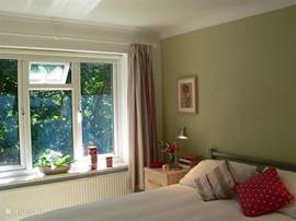 The master bedroom has windows on two sides overlooking the garden.