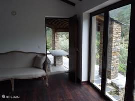 Sofa in grote slaapkamer met deur naar het terras.