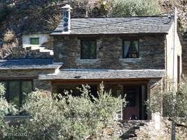 Voorgevel van huis die omgeven is door olijfbomen.