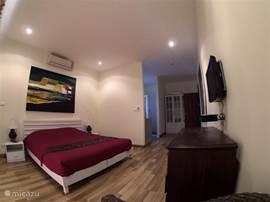 Slaapkamer met kingsize bed en flatcreen tv
