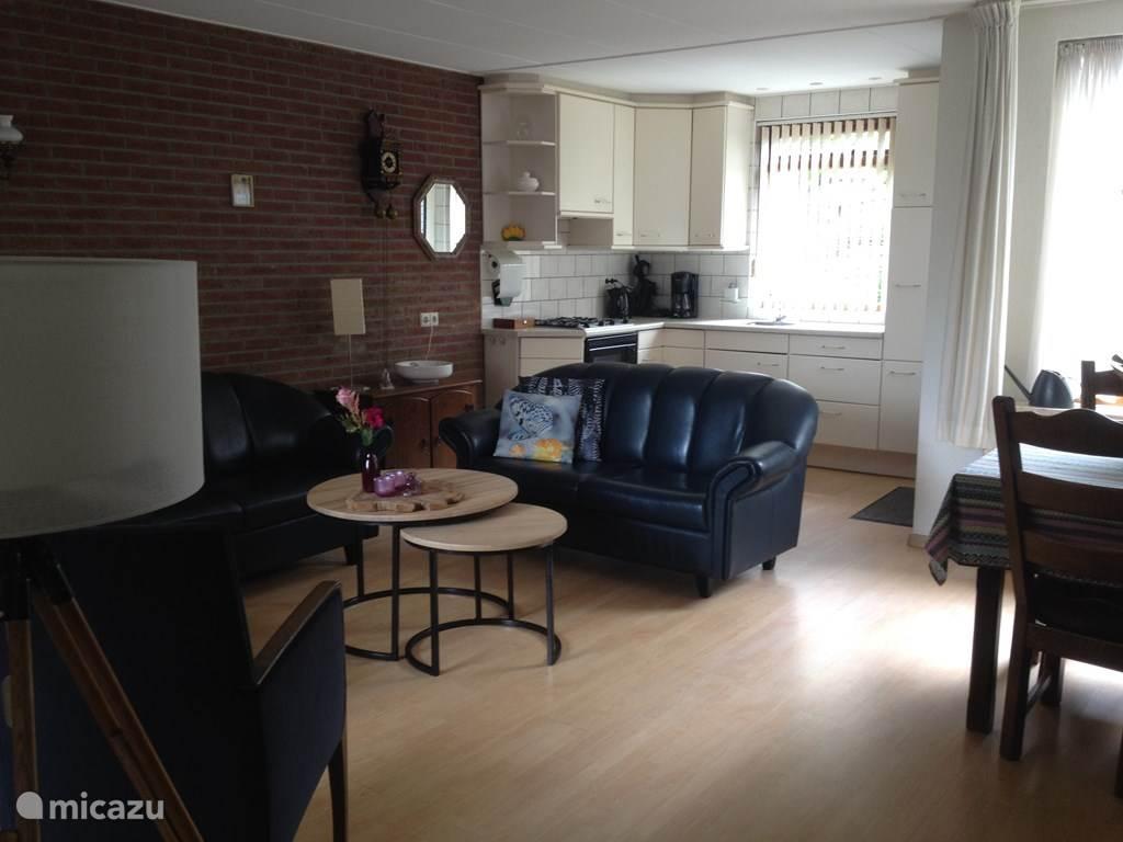 Zonnige woonkamer met open keuken en eethoek