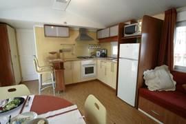Open keuken met barretje en 2 hoge stoelen.