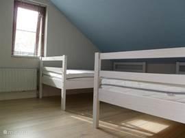 Slaapkamer met twee eenpersoonsbedden en kledingkast en zitje