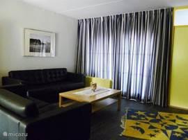 De woonkamer met een twee- en driezitbank, flatscreen tv,  open haard en schuifpui.