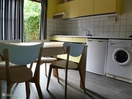 Keuken met gaskookplaat, koelvriescombinatie, magnetron en wasmachine.