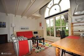 De woonkamer is ligt en vrolijk ingericht met uitzicht om het eigen terras.