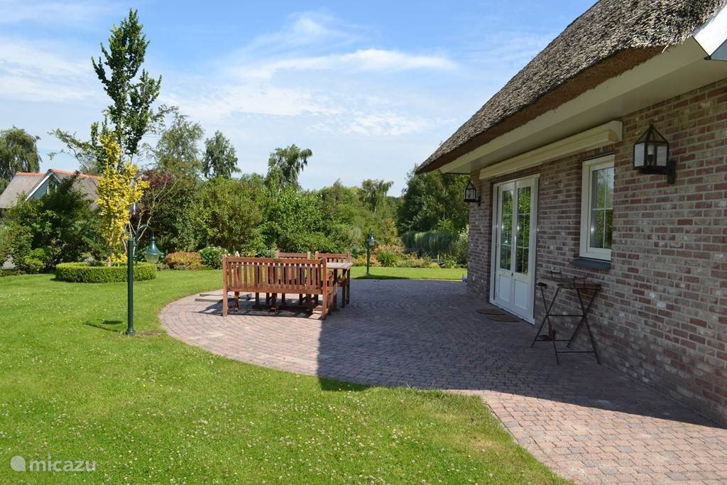 De openslaande tuindeuren naar het terras met tuinmeubilair. In de prachtige grote tuin!
