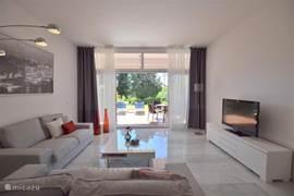Ruime huiskamer met grote pui naar het gedeeltelijk overdekte terras; waar men zowel in zon als in schaduw kan zitten.