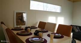 De eettafel heeft zes stoelen en een kinderstoel.