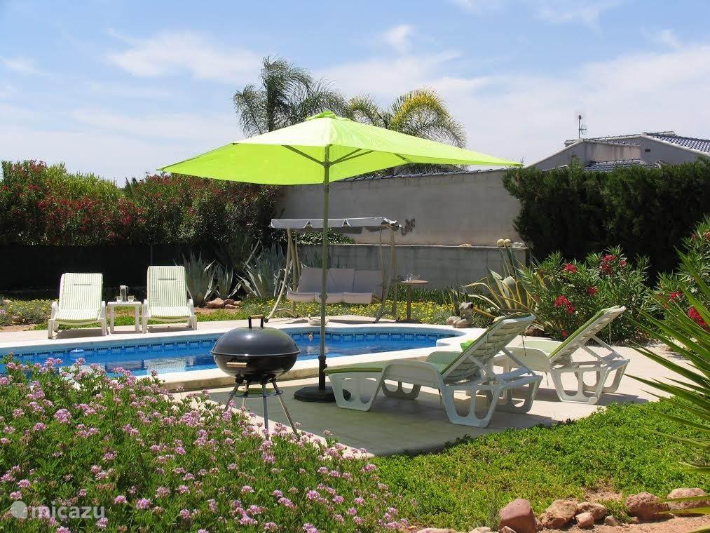 Tuin, zwembad, schommelstoel en ligstoelen