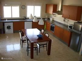 Overzicht Keuken met koelkast, diepvriezer, afwasmachine, wasmachine, oven, magnetron en een 4 pits elektrisch kookplaat.