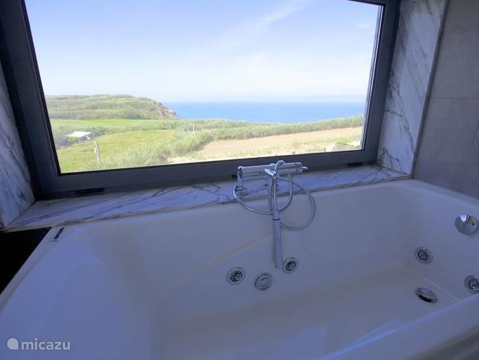 De badkamer die speciaal gemaakt is op de bovenste verdieping en voorzien van een raam met uitzicht op de achtertuin en de zee. De badkamer is voorzien van een wastafel, toilet en bubbelbad. Heerlijk relaxen in bad met de ondergaande zon. In de vensterbank uw hapje en drankje. Komt u er nog uit?