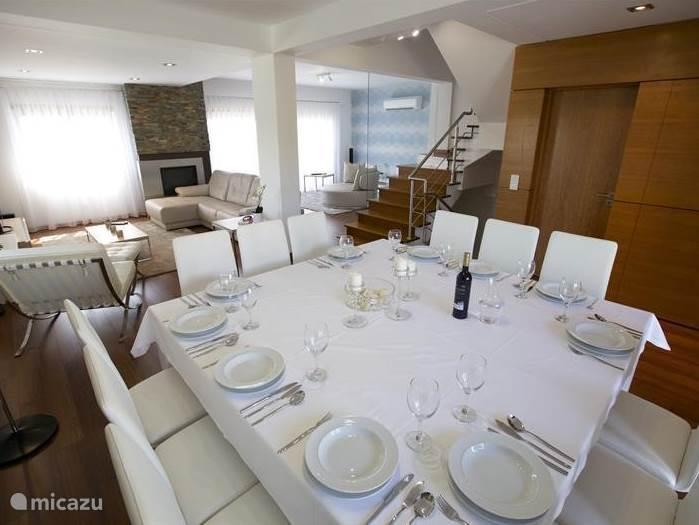 Een ander aanzicht in de woonkamer met de grote eettafel met 12 stoelen.