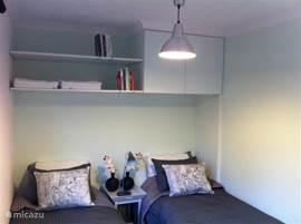 In deze slaapkamer staan twee identieke bedden. Zij zijn ook tegen elkaar te plaatsen. Naast de bergruimte boven de bedden, staat er ook een zgn meidenkast in de kamer.