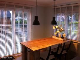 De op maat gemaakte steigerhouten tafel met grote lampen erboven geven ook een knus gevoel. Dit in een ruim en licht chalet van 70m2.