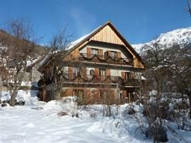Chalet Solneige in de winter. Een heerlijk plekje op een zonnig terras met prachtig uitzicht over de bergen en het meer.