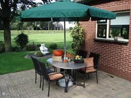 Het tuinzitje naast de woning, er zijn 4 vaste tuinstoelen, 2 verstelbare stoelen, een bbq en de tafel met parasol uiteraard.