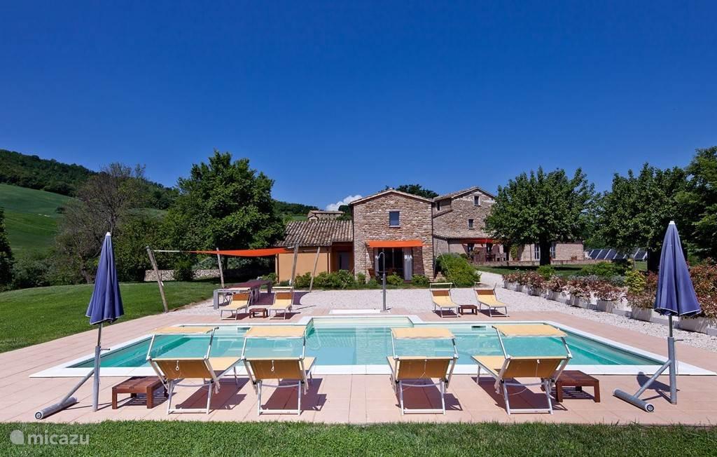 gevelaanzicht appartement Annesso, daarvoor zwembad en van schaduwdoek voorzien terras met tafels en stoelen voor velen