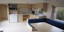 Ruime frisse woonkamer met complete U-vormige keuken.