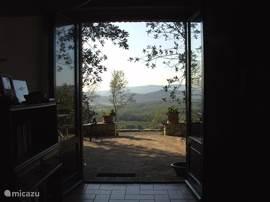 openslaande deuren naar privéterras met uitzicht over de heuvels.