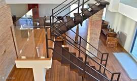 Karakteristieke trap naar de eerste etage dat centraal staat in de woning