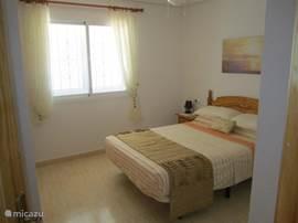 ruime slaapkamer met een tweepersoonsbed en ingebouwde kleerkast en airco