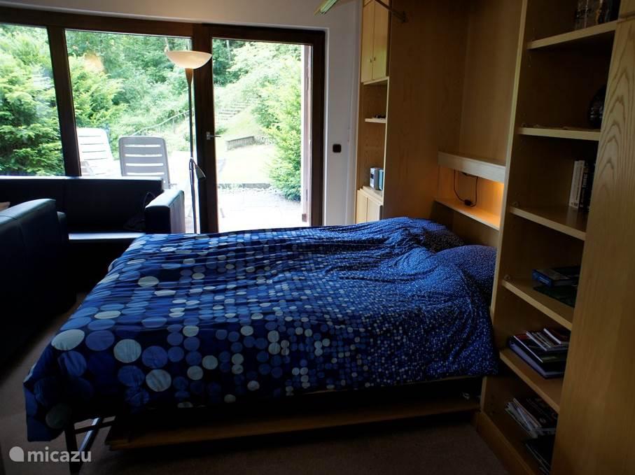 In de woonkamer staat een comfortabele lits-jumeaux, deze is eenvoudig weg te klappen in de kastenwand.  Dit is géén bedbank maar een volwaardig zeer comfortabel bed. Uw beddengoed kunt u gewoon erop laten liggen als u het bed opklapt.