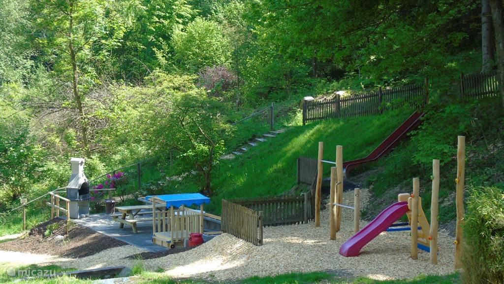 De tuin met diverse speeltoestellen en de bbq-plaats
