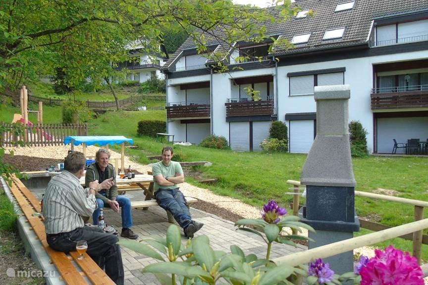 Het heerlijke gemeenschappelijke terras met bbq in de grote tuin