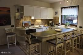 Ruime hoekkeuken met eetbar. Volledig uitgerust met oa. waterkoker, koffiezetapparaat, oven, koelkast met vriesvak, 4-pits fornuis met afzuigkap en broodrooster.