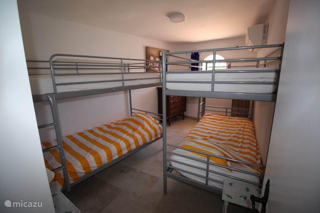 derde slaapkamer met twee stapelbedden en uitzicht op zwembad en zee