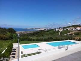 Zicht vanuit de villa op de twee gemeenschappelijke zwembaden, het natuurgebied en de Oceaan.  Ook zicht op stadje Nazare.