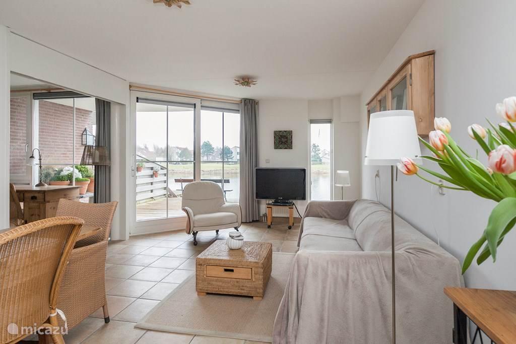 Een ruime woonkamer, grenzend aan het terras,  met links schuifdeuren naar de slaapkamer, waar u ook in alle rust kunt werken aan een bureau.