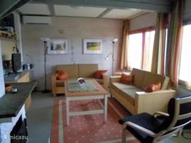 Zithoek in de woonkamer voorzien van 2 banken en een stoel.