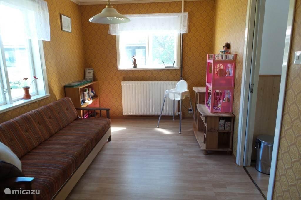 Naast de keuken ligt een extra kamer. Deze kamer kun je onder andere gebruiken als speelkamer voor de kids of bijvoorbeeld als slaapkamer. Er hangen verduisterende rolgordijnen en door middel van schuifdeuren kun je de kamer afsluiten.
