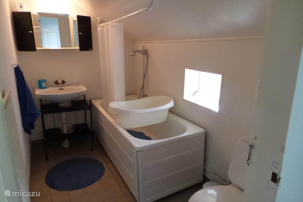 Fris je op in de badkamer met wastafel, toilet en bad (zittend douchen). Een kinderbadje is aanwezig.
