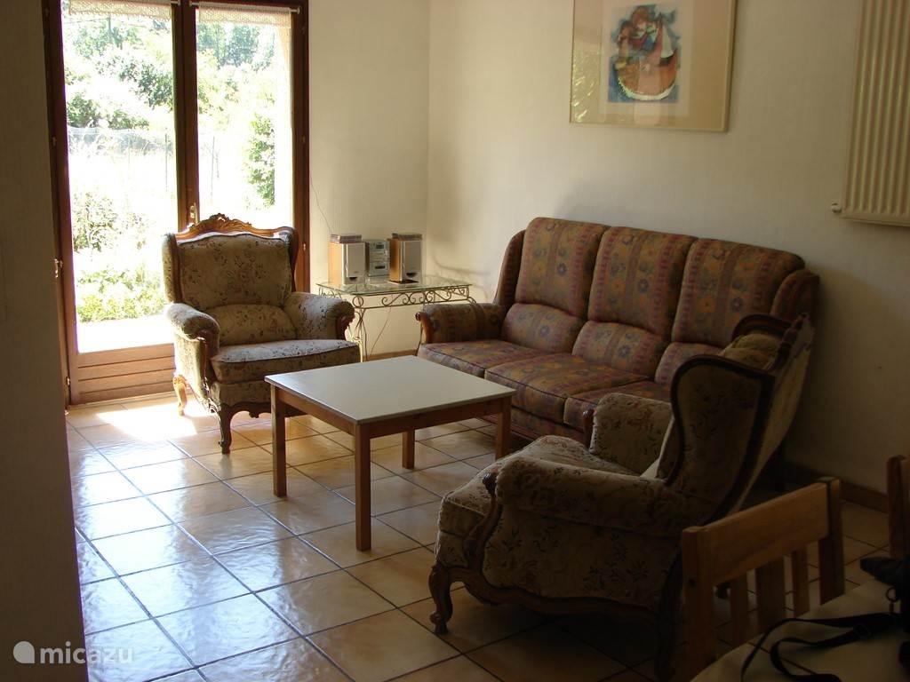 salon met open haard, grote zetel en twee zetels zicht op de tuin