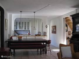 Fijne lange kloostertafel met zicht op de keuken en de woonkamer.