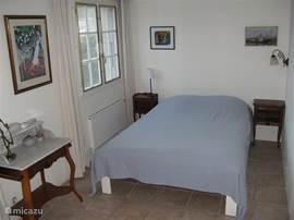 Lichte ruime slaapkamer op woonverdieping met tweepersoonsbed.