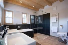 Luxury bathroom with bath, shower, radiator, wash basin and toilet.