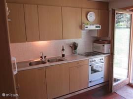 Keuken met 3-pits electrisch fornuis met oven, magnetron, Senseo, waterkoker, koelkast met vriesvak.