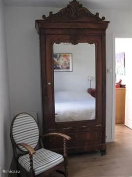 Antieke kledingkast met spiegel en doorkijk naar kinderkamer.