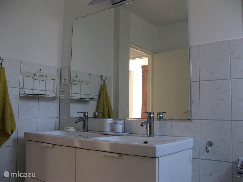 Badkamer met dubbele wastafel, toilet en douche