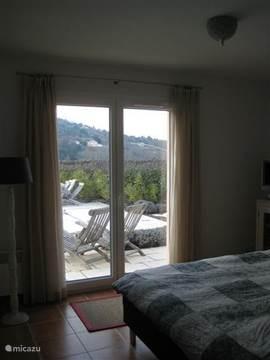 De slaapkamer aan de achterzijde beneden met uitzicht op het terras, het verwarmde zwembad en de tuin. De slaapkamer heeft een groot tweepersoonsbed en kast.