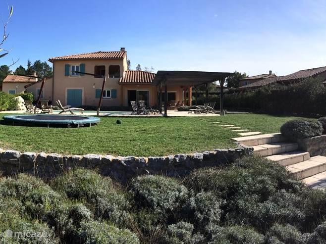 Een heerlijk tuin met verwarmd zwembad en trampoline en verschillende zonneterassen.