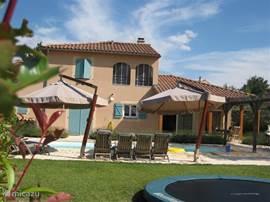 De villa vanuit de tuin gezien met de trampoline voor de kinderen.