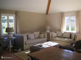 De grote en gezellige zitkamer, voorzien van knusse houtkachel.